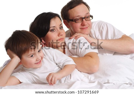 Beautiful Caucasian happy family of three on the bed
