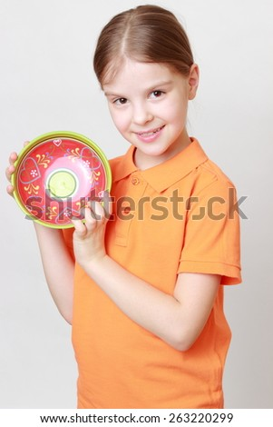 Beautiful caucasian little girl holding colorful ceramic bowl - stock photo