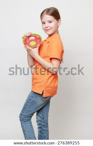 Beautiful caucasian little girl holding colorful ceramic bowl - stock photo