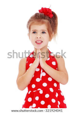 Beautiful Caucasian little girl in red summer dress with polka dots and a red bow on his head folded on his chest in the face of the hand. Closeup-Isolated on white background - stock photo