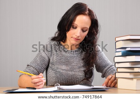 Beautiful caucasian mature student at home, sitting to her desk studying with work books stacked nearby. - stock photo