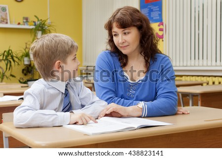 beautiful caucasian mature teacher and elementary school student sitting at a desk and looking at each other. - stock photo