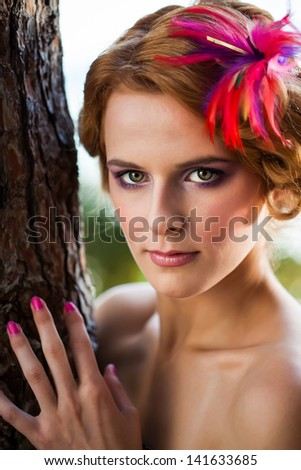 beautiful caucasian model with red curly hair pinned up with a feathered flower leaning against a big old tree - stock photo