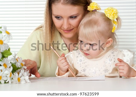 Beautiful Caucasian mother and happy daughter sitting at a table near the window