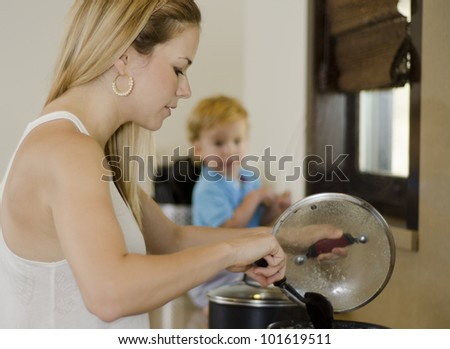 Beautiful caucasian mother cooking while son watches in the background