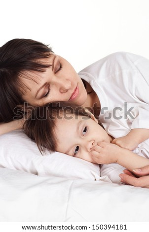 beautiful Caucasian mum with her daughter lying in bed