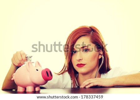 Beautiful, Caucasian nurse listening to a piggy bank with a stethoscope. Isolated on white  - stock photo