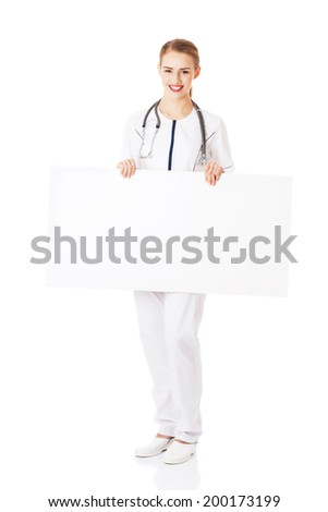 Beautiful caucasian nurse or doctor holding empty white board. Isolated on white. - stock photo