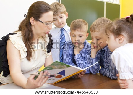Beautiful Caucasian primary school teacher reading a book at the table. Three boys and a girl, pupils stand by and listen. Horizontal color image.