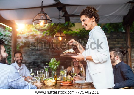 Beautiful Caucasian smiling woman putting a plate with meal on dining table at backyard celebration.