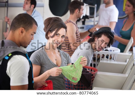 Beautiful Caucasian stares at handsome Black man with panties in her hands at the Laundromat - stock photo