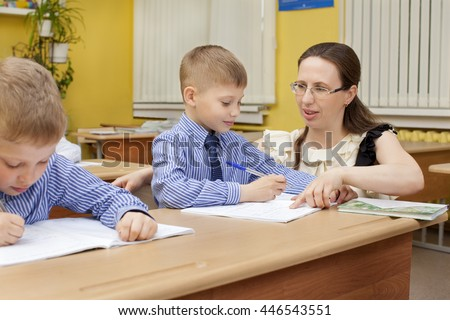 beautiful caucasian teacher checks the notebook in an elementary school student. They sit at a desk in the classroom.