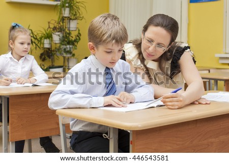 beautiful caucasian teacher checks the notebook in an elementary school student. They sit at a desk in the classroom. - stock photo