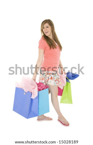 Beautiful Caucasian teenager holding shopping bags while standing on a white background