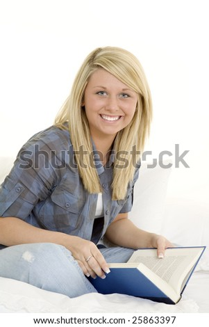 Beautiful Caucasian teenager laying in bed reading a book