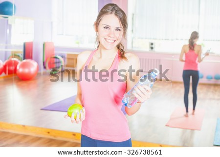 Beautiful Caucasian woman after fitness exercise holding green apple and natural water at plastic bottle. Eating, sport and healthy lifestyle concept - stock photo