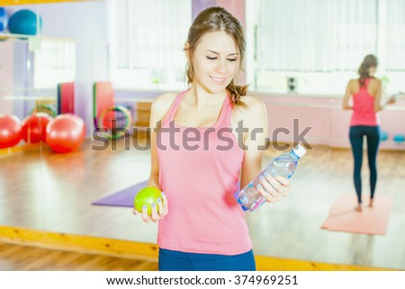 Beautiful caucasian woman after fitness exercise, holding green apple and natural water at plastic bottle. Eating, sport and healthy lifestyle concept - stock photo