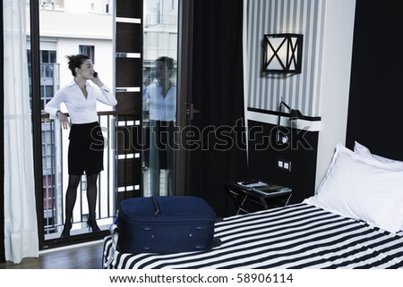 beautiful caucasian woman arrival in a hotel bedroom phoning - stock photo