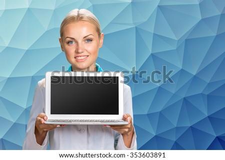Beautiful Caucasian woman doctor holding a laptop computer  - stock photo