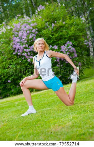 Beautiful caucasian woman doing stretching exercises in the park - stock photo