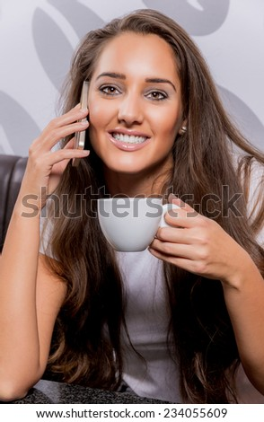 Beautiful caucasian woman having a coffee and talking phone. - stock photo