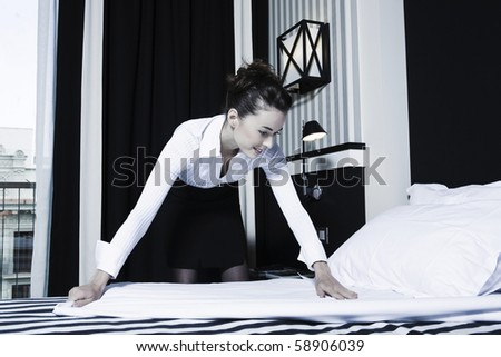 beautiful caucasian woman housekeeper doing bed in a hotel bedroom - stock photo