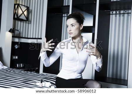 beautiful caucasian woman in a bedroom drying nails - stock photo