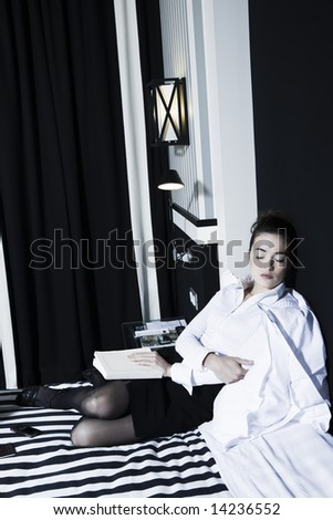 beautiful caucasian woman in a hotel bedroom - stock photo