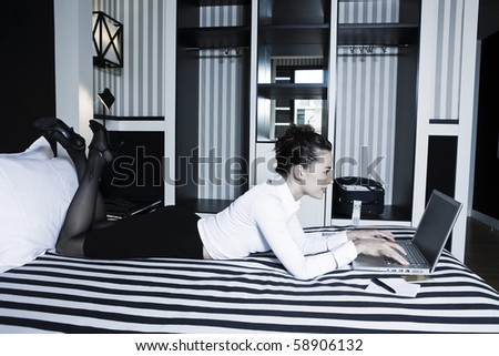 beautiful caucasian woman in a hotel bedroom computer internet surfing - stock photo