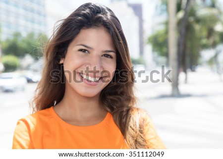 Beautiful caucasian woman in a orange shirt in the city - stock photo