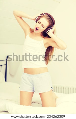 Beautiful caucasian woman in pijamas is listening to music on bed. Indoor background. - stock photo