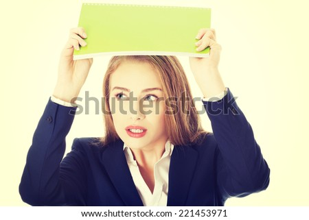 Beautiful caucasian woman is holding notebook over her head, protecting herself. Isolated on white.