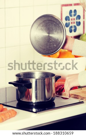 Beautiful caucasian woman is standing in kitchen and cooking.