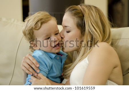 Beautiful caucasian woman kissing her son on the cheek