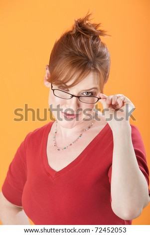 Beautiful Caucasian woman looks sneakily from over her eyeglasses - stock photo