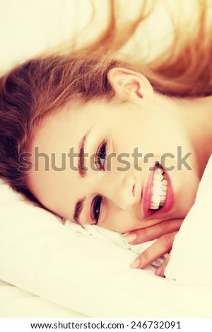 Beautiful caucasian woman lying in bed at home. - stock photo