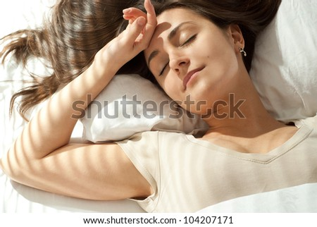 Beautiful Caucasian woman lying on a pillow on a light background - stock photo