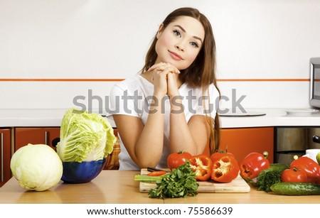 beautiful caucasian woman preparing salad in the kitchen. - stock photo
