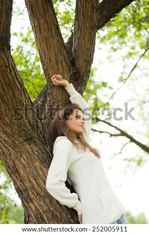 Beautiful caucasian woman relaxing near the tree at summer - stock photo