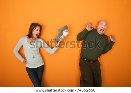 Beautiful Caucasian woman scaring man with a fur toy - stock photo