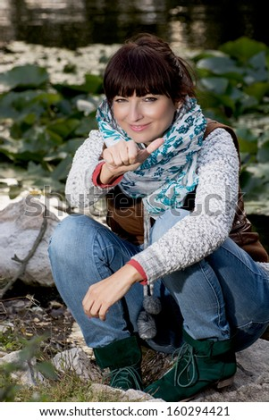 Beautiful caucasian woman showing thumbs up in outdoors. - stock photo