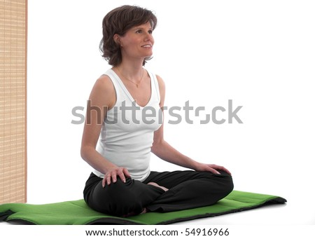 Beautiful caucasian woman sitting on yoga mat, smiling and looking relaxed