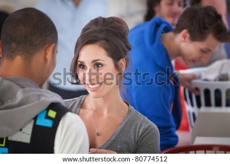 Beautiful Caucasian woman smiles at a guy in the laundromat - stock photo
