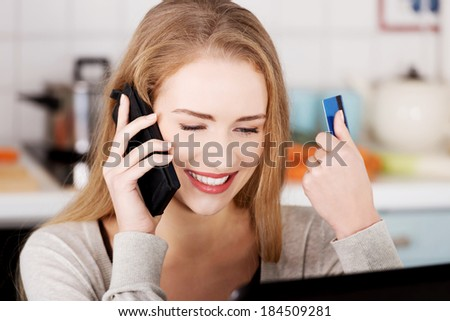 Beautiful caucasian woman talking through phone and working with laptop. Indoor background.