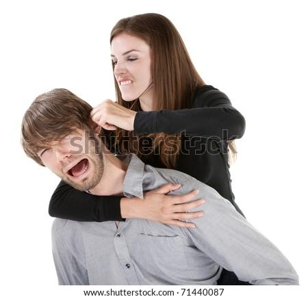 Beautiful Caucasian woman twisting boyfriend's ear while he screams - stock photo