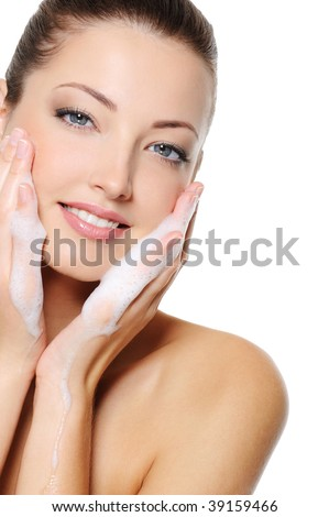 Beautiful caucasian woman washing her beauty health face with foam on her hands - stock photo