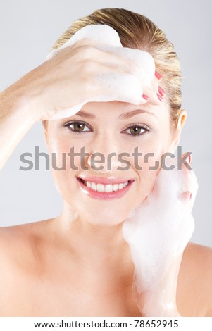 Beautiful caucasian woman washing her face with foam - stock photo