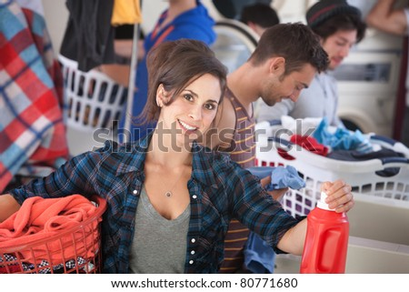 Beautiful Caucasian woman with clothes basket and detergent in the laundromat - stock photo