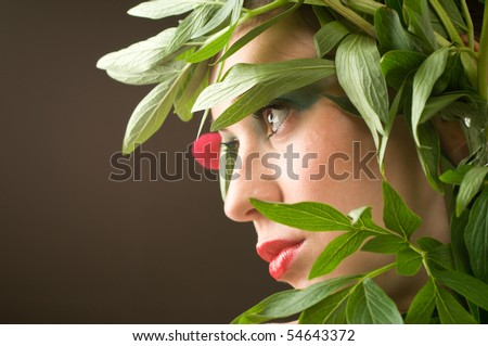 Beautiful caucasian woman with leaves of flower around her head