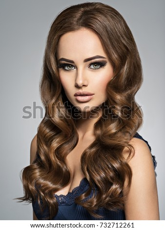 Beautiful Caucasian Woman With Long Brown Curly Hair. Portrait Of A Pretty Young  Adult Girl